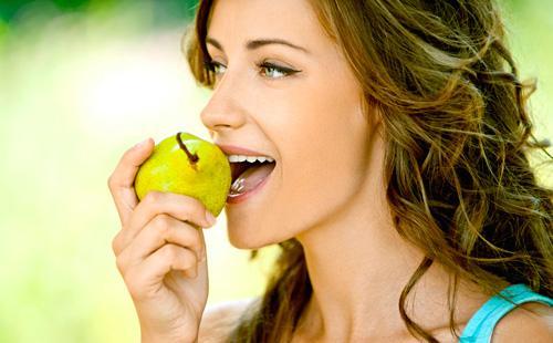 Девушка ест грушу
